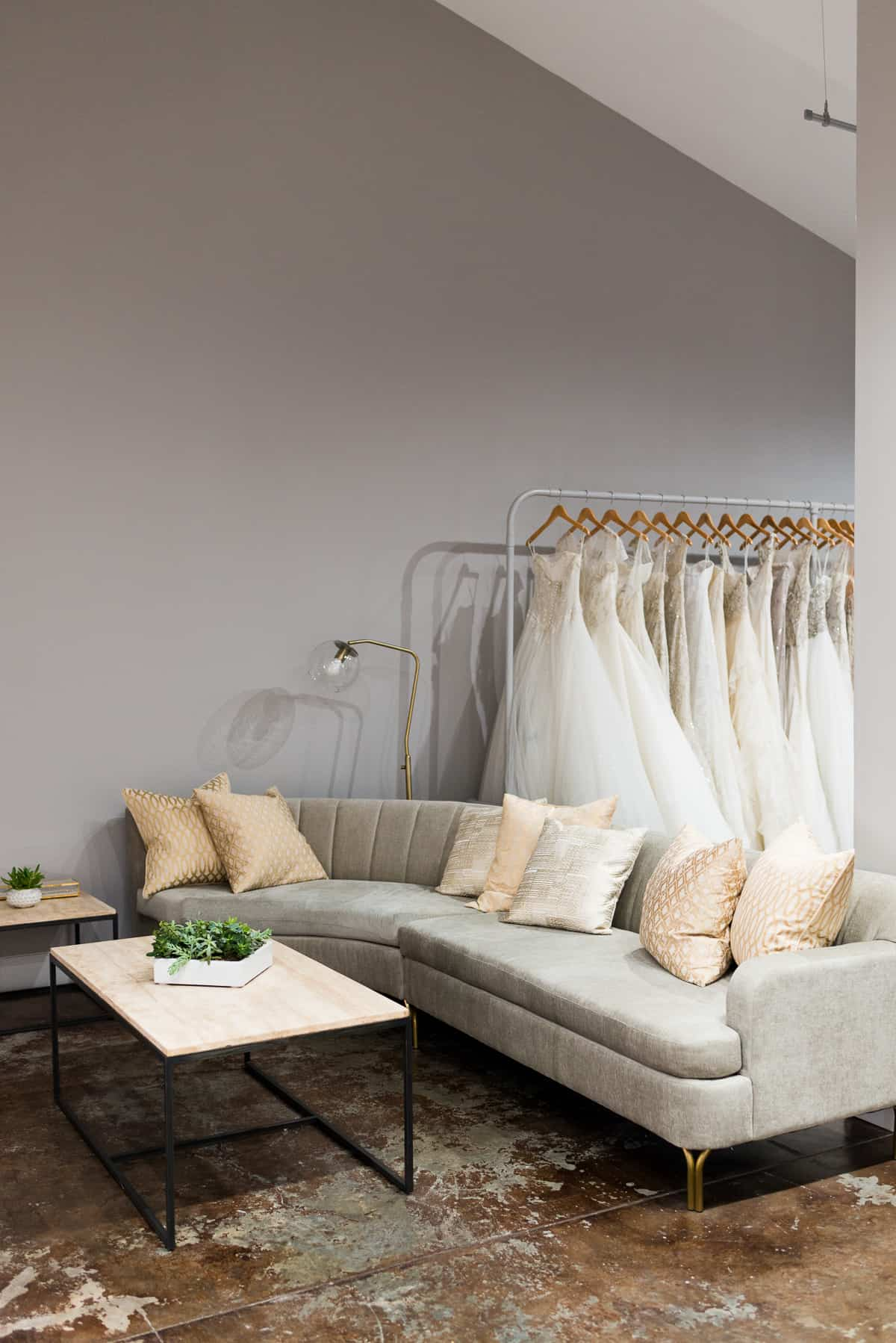 grey couch white with wood and metal coffee table and white wedding dresses at The Bridal Finery