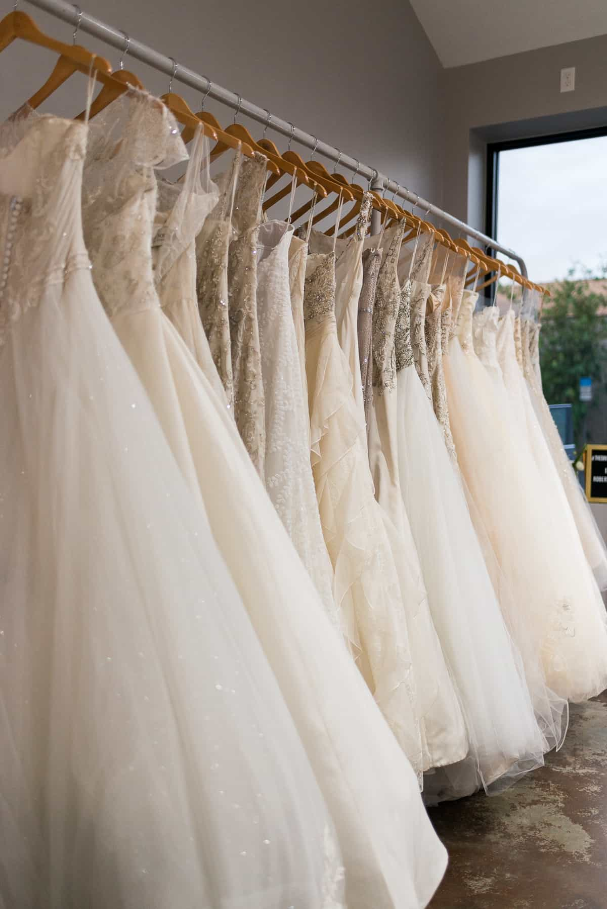 whtie wedding dresses on wooden hangers at The Bridal Fienry