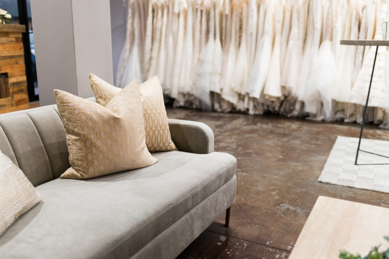 grey couch with gold and white pillows and white wedding dresses at The Bridal Finery