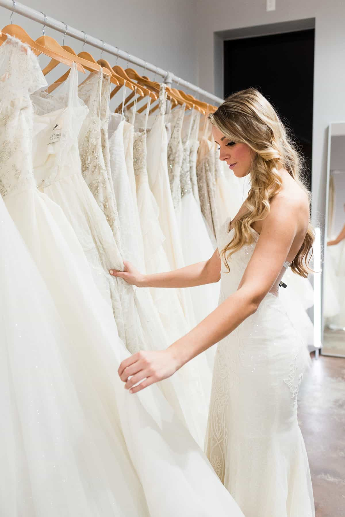 bride in white wedding dress looking at rack of white wedding dresses hanging at The Bridal Finery