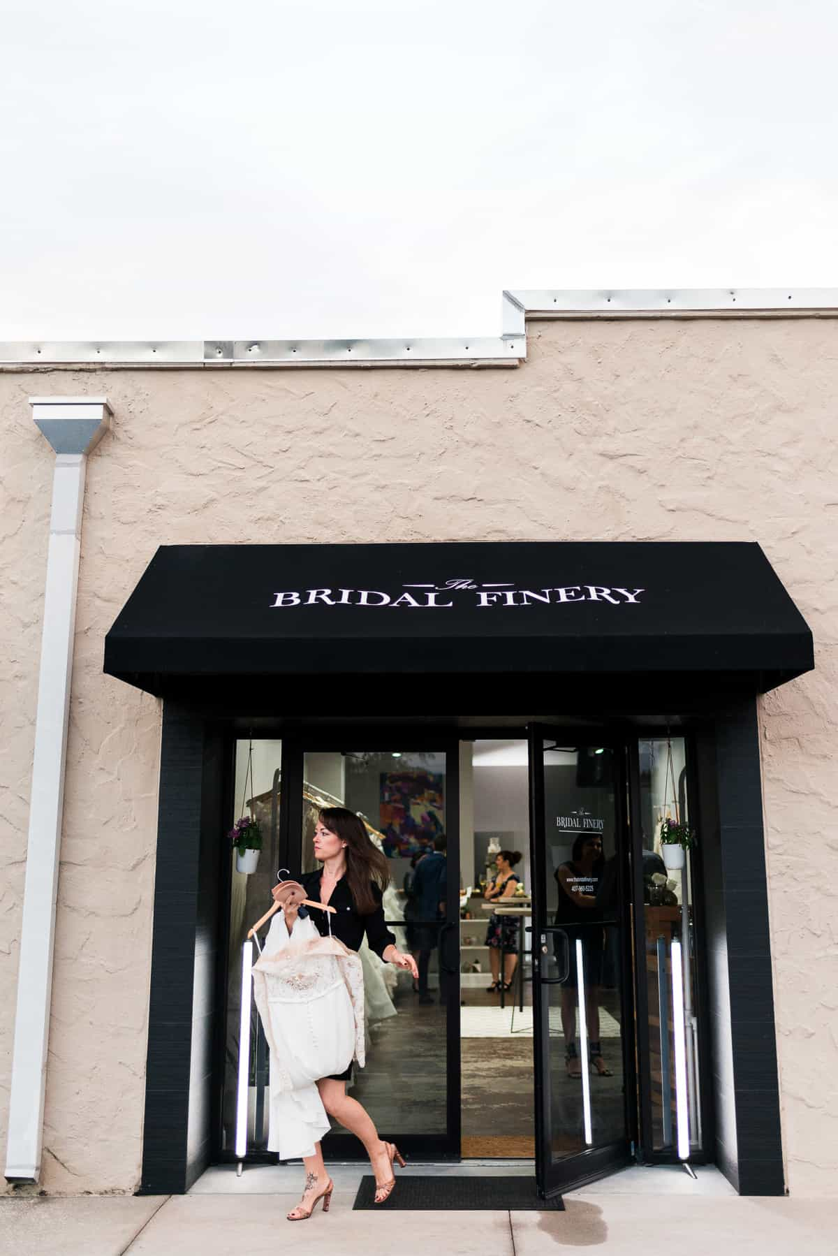 bride walking out of The Bridal Finery dress boutique with wedding gown in hand