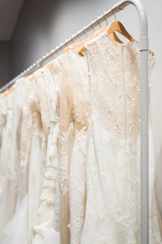 rack of white designer wedding dresses at The Bridal Finery
