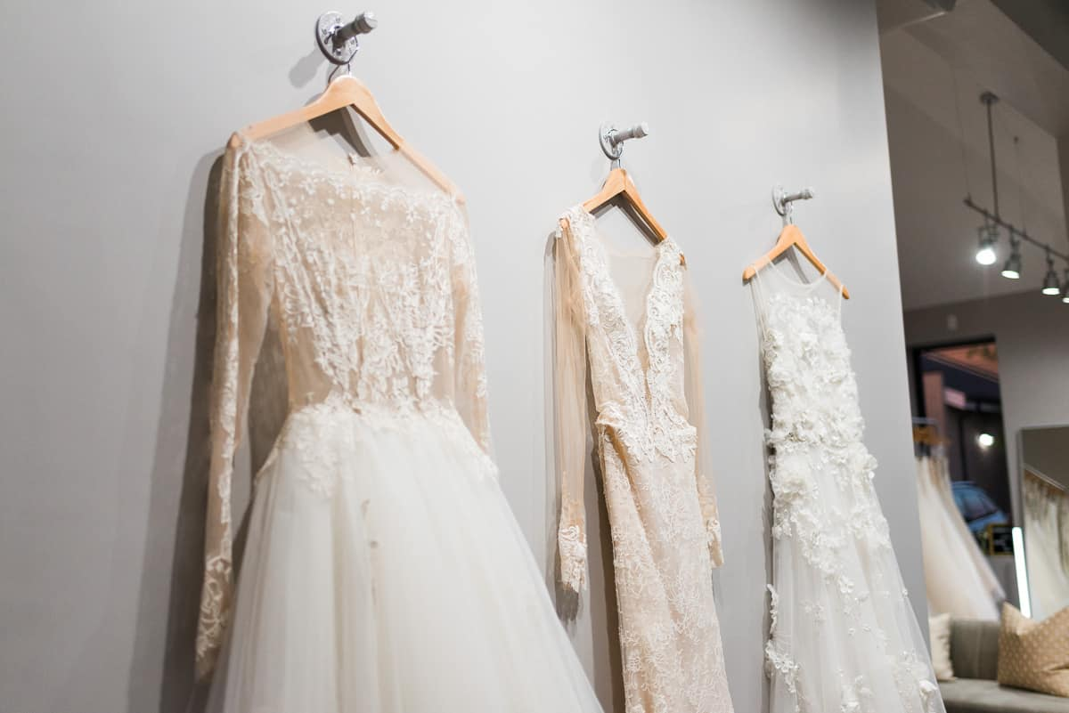 three designer wedding dresses hanging on the wall of The Bridal Finery