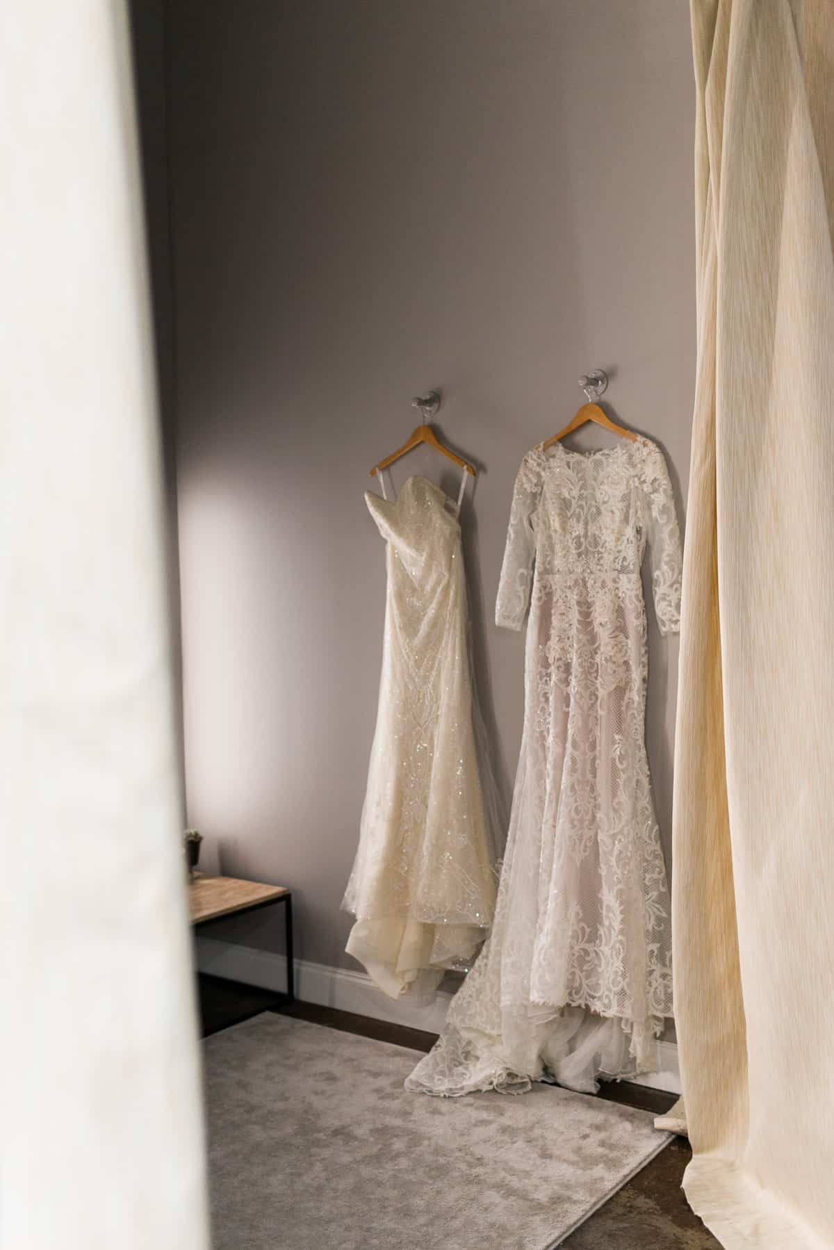 white and ivory designer bridal gowns hanging in The Bridal Finery dressing room