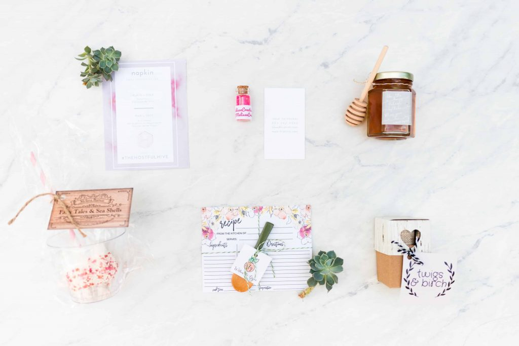 Favors on marble back ground, grey and pink print, glass jar of hot pink sprinkles, hexagon jar of honey with wooden honey dipper, red and pink sprinkled marshmallow, pink and yellow recipe card with hand painted wooden spoon with green handle, wood grain gift back with heart cut out