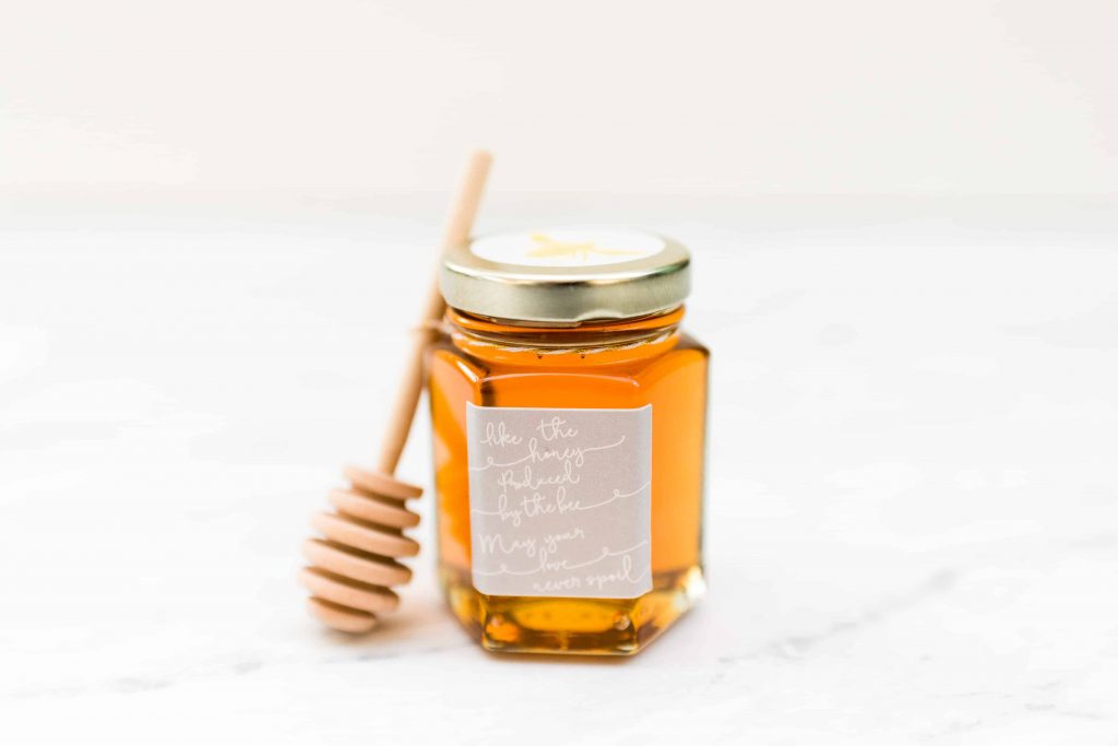 "4 ounch hexagon glass jar filled with honey with wooden honey dipper and grey and white sticker that reads ""like the honey produced by the bee, may your love never spoil"""