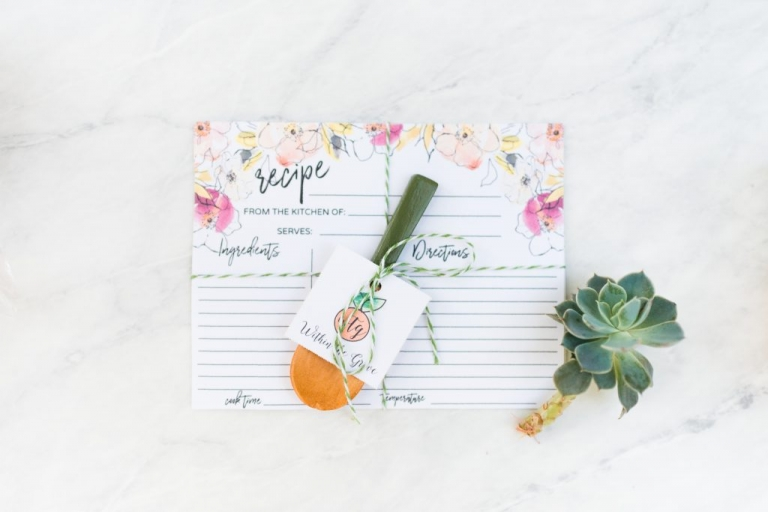 Pink and yellow floral recipe card with black text, hand painted wooden spoon with green handle wrapped with gift tag, green succlent on corner of card