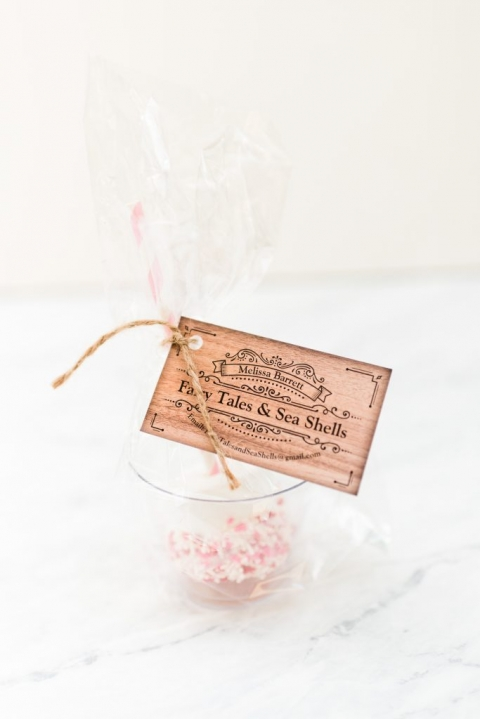 Pink and red sprinkle covered marshmallow in clear cup with cellophane wrapper, tied with twine and wood grain business card
