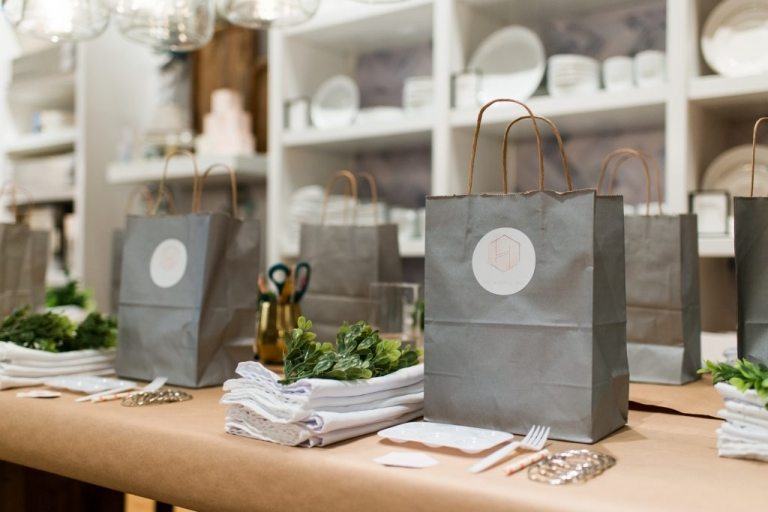 Grey gift bag on table covered in kraft paper with white napkins, boxwood garland and paint tools set on table