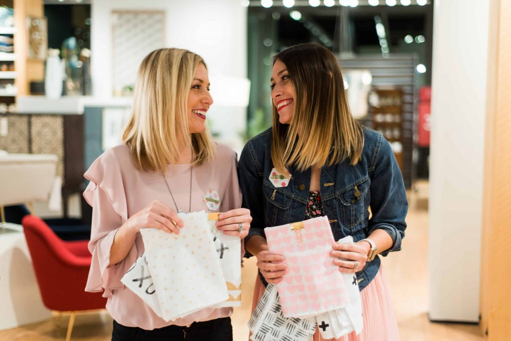 blonde and brunette sisters looking and smiling at eachother with DIY linen napkins west elm orlando workshop