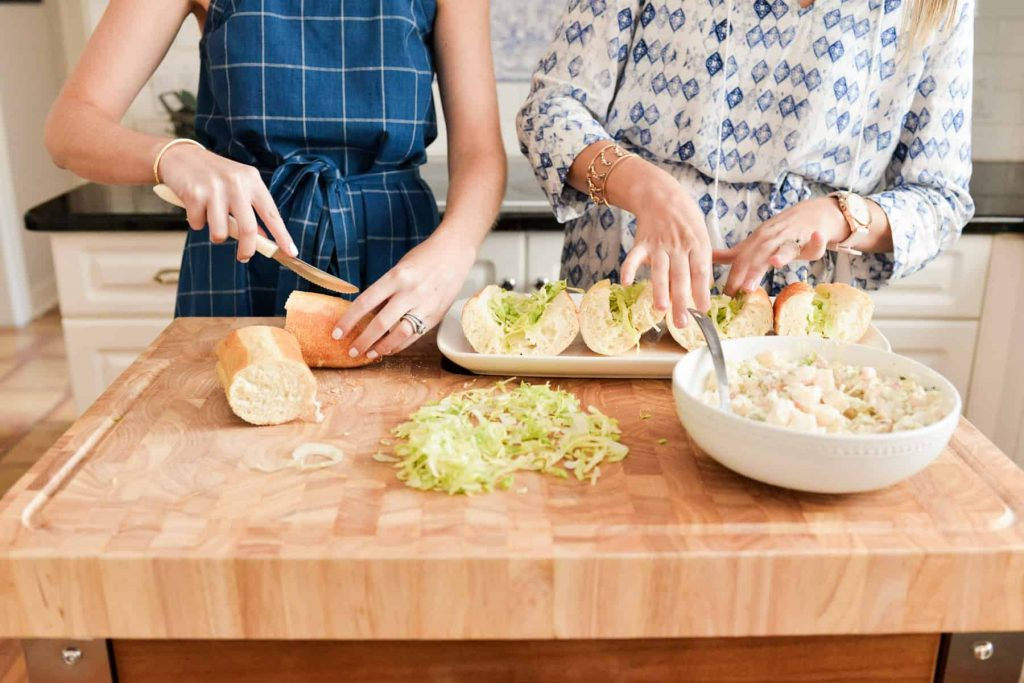 two females in blue and white dresses making sandwiches on butcher block