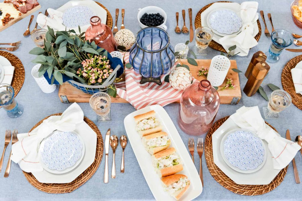 red white and blue fourth of july tablescape with platter of new england style shrimp rolls on white sub roll