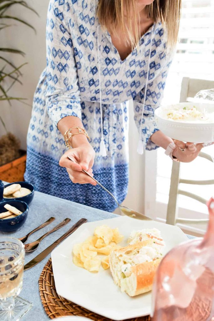 female in blue and white dress holding a bowl of coleslaw and spooning it onto a white dinner plate
