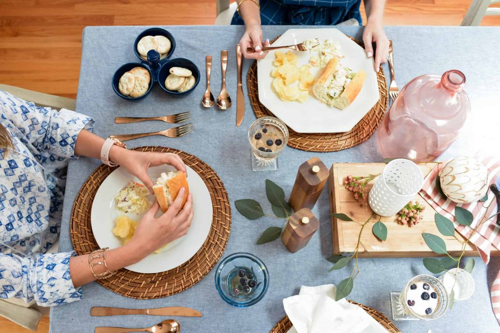 Two females eating new england style shrimp rolls and coleslaw on fourth of july tablescape