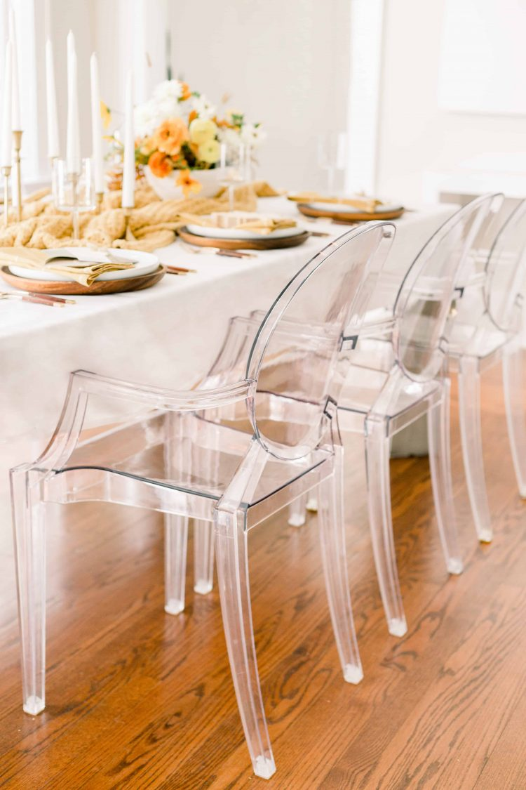 thanksgiving tablescape dressed in off white linen and fall colored decor and ghost chairs