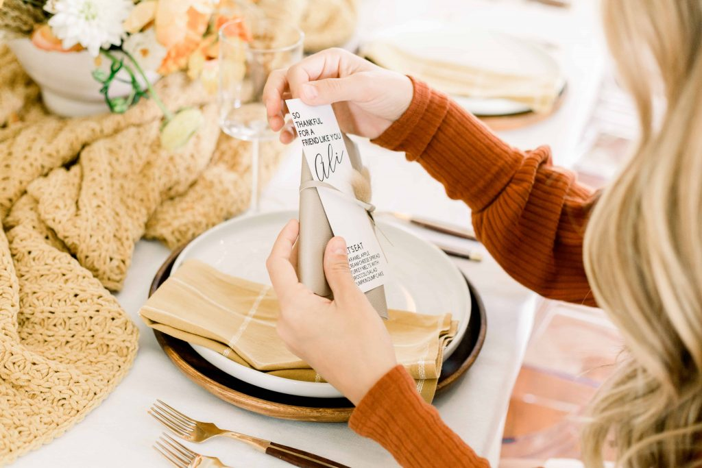 blonde female in amber sweater holding tan leather clutch with place card for friendsgiving