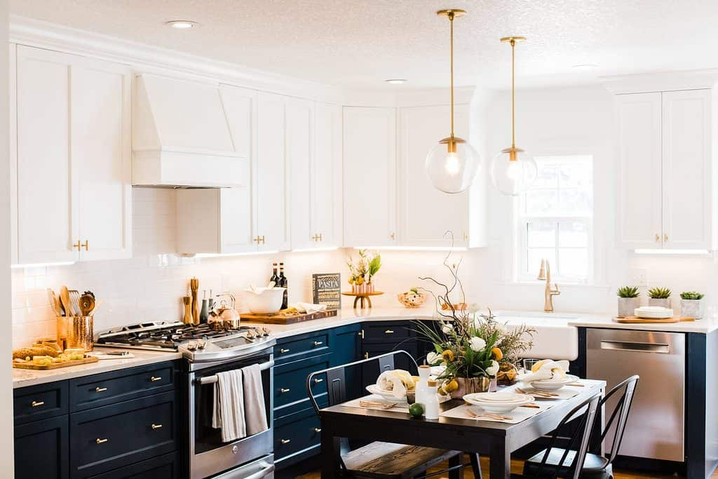 white and navy kitchen with gold accents and dark wood dining table set for guests