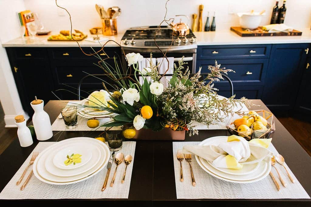dark wood dining table set with white kate spade plates with lemons and copper flatware and fall inspired centerpiece