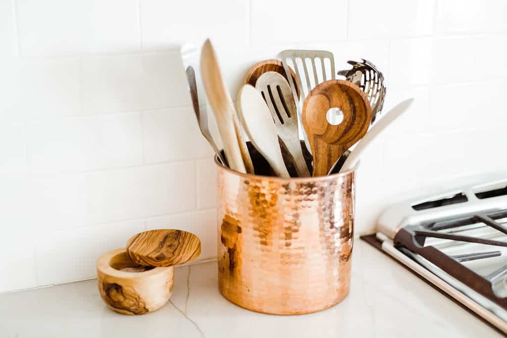 close up of copper utensil holder filled with serving utensils