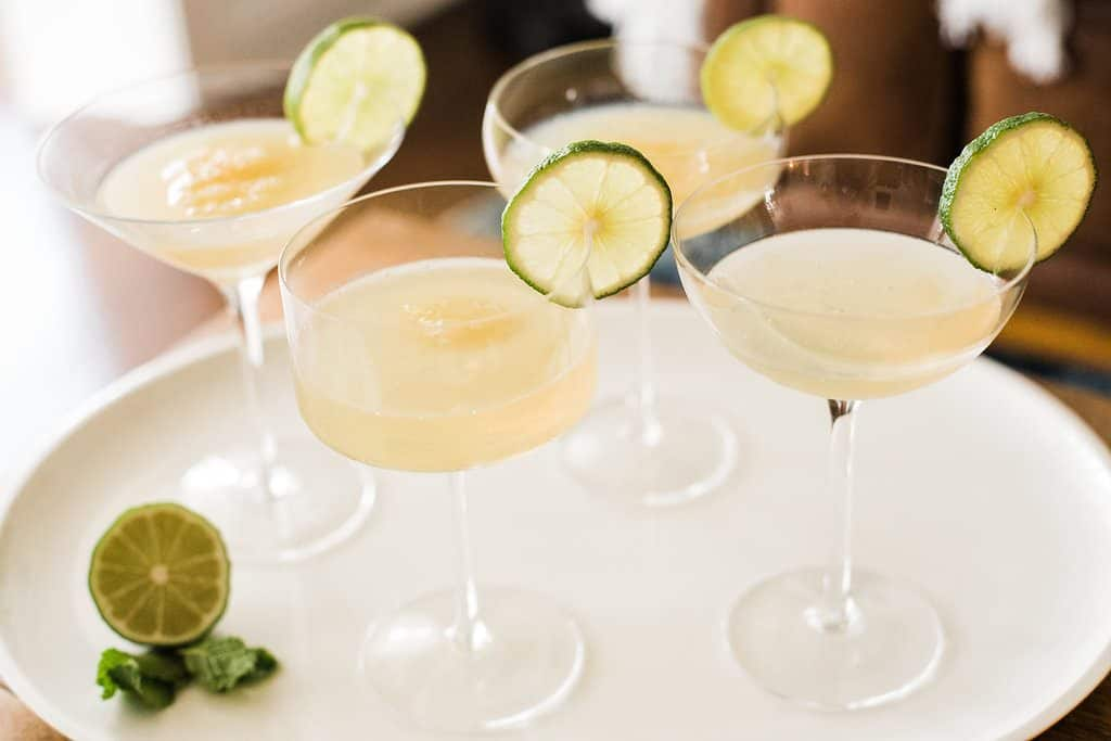 four clear stemmed glasses with frozen margaritas on white platter