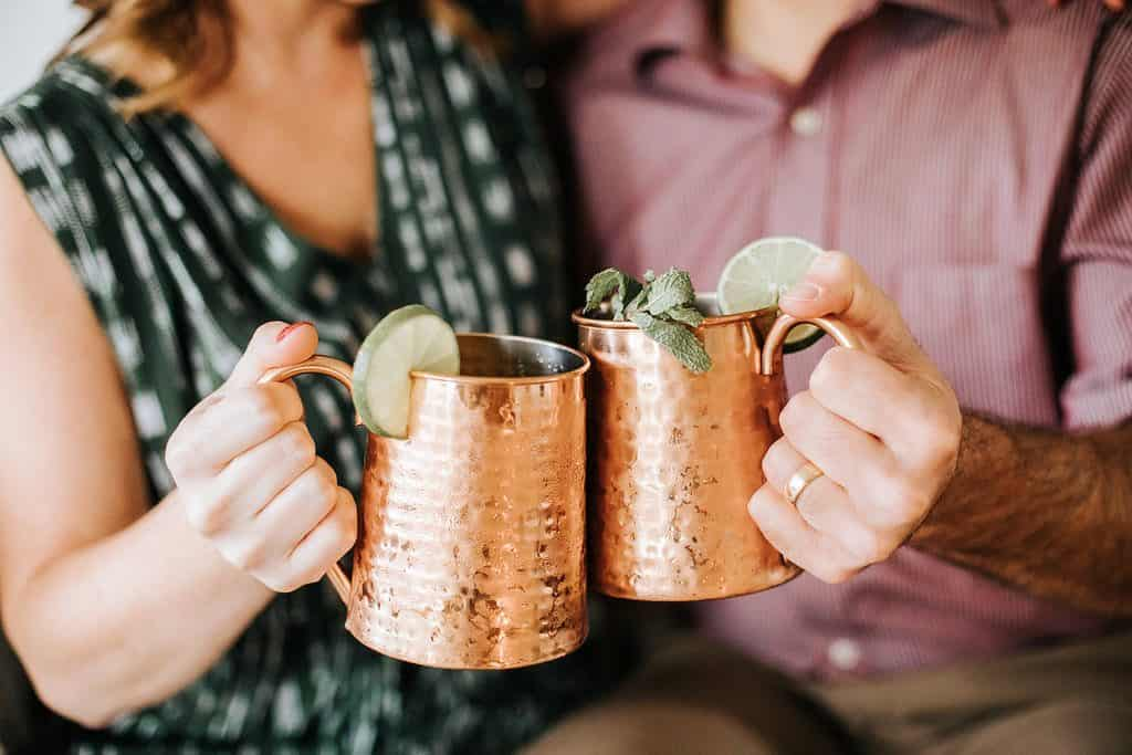 close up of female in green dress and male in maroon button up shirt toasting with copper mugs