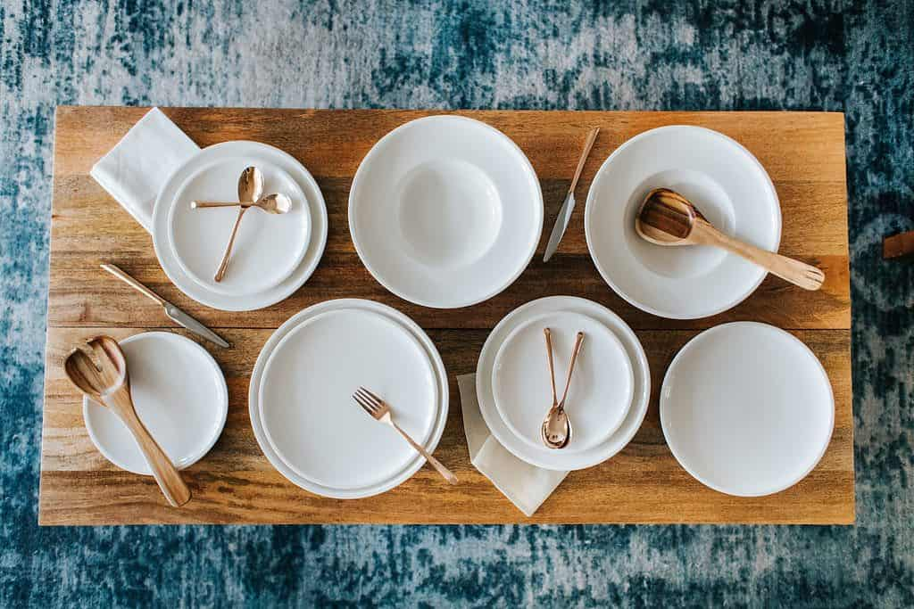 overhead shot of stacked white plates and copper flatware on wood coffee table and blue west elm rug