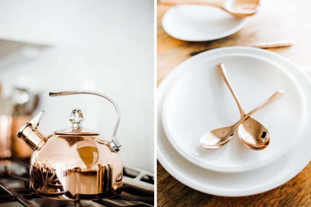 close up of copper tea kettle and white plates with copper spoons