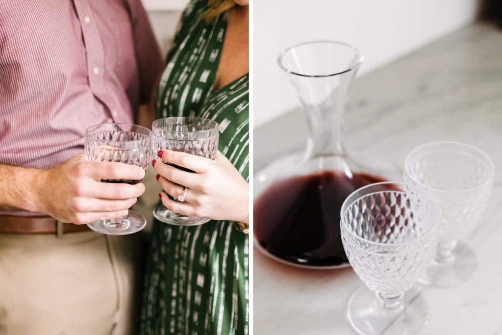 close up of male in maroon button up shirt and female in green dress toasting with clear crystal wine glasses and closeup of clear red wine decanter and two clear crystal wine glasses