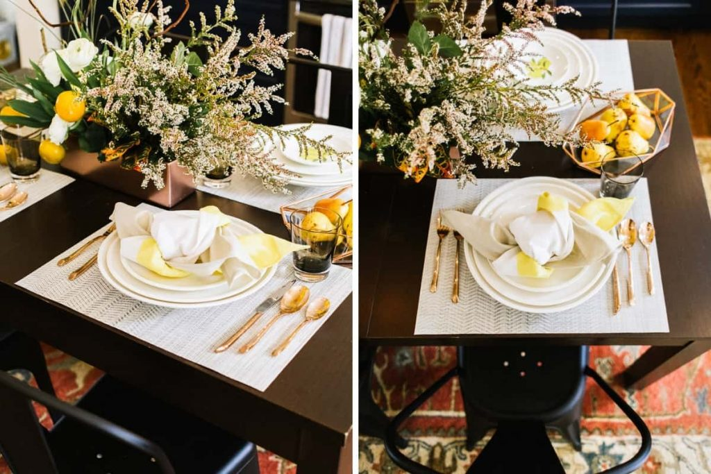 close up of dark wood dining room table set with white dinner plates and copper flatware and fall inspired centerpiece
