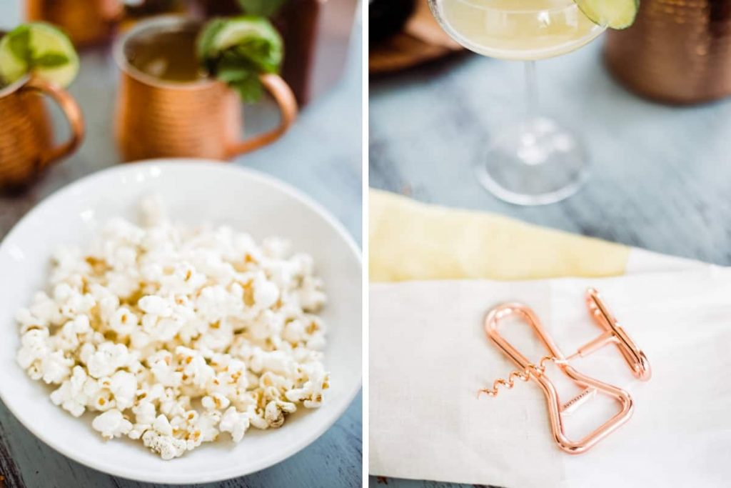 close up of white bowl of popcorn and white and yellow linen napkin with copper wine and bottle opener