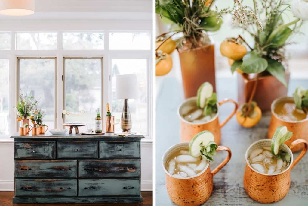 distressed dresser styled with barware copper mugs wood cake stand whiskey and champagne in copper bucket and close up of copper mugs with frozen margarita