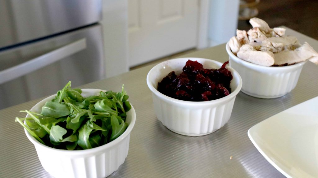 arugula, cranberry sauce and carved turkey on kitchen counters