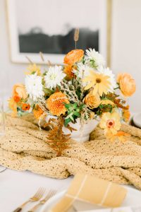 fall colored low floral arrangment in white bowl on mustard colored table runner