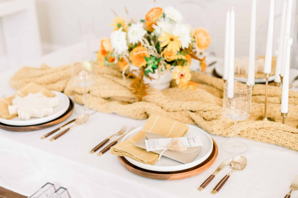 fall tablescape with mustard blanket table runner and floral centerpiece wood charger white dinner plate and gold plaid linen napkins
