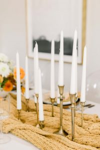 group of gold taper candle holders with white taper candles on mustard colored blanket on dining table