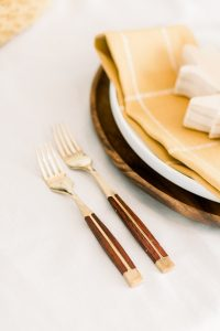 gold and wood dinner and salad forks next to wood charger white dinner plate and gold napkin