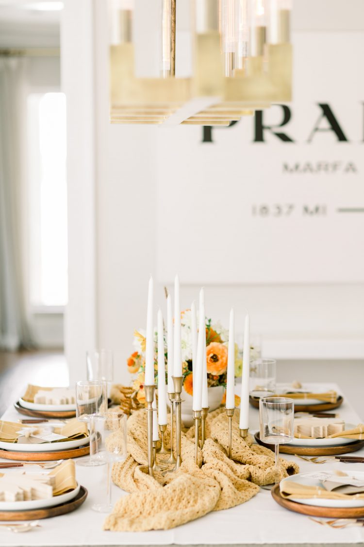 bright dining room with dining table set for fall in front of large prada sign and gold chandelier