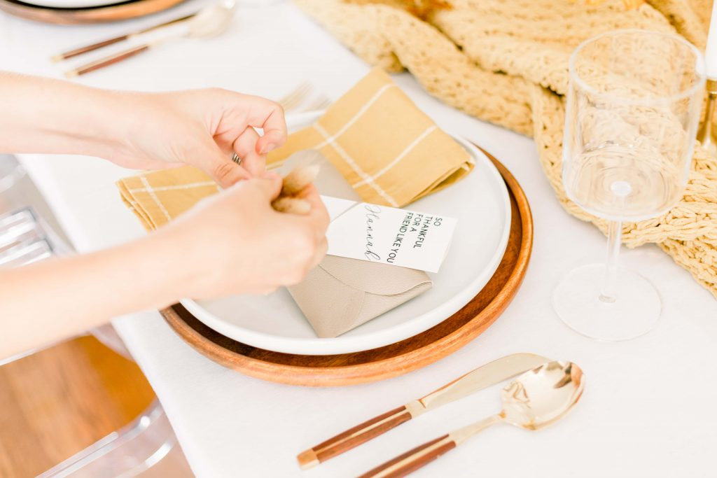 DIY Leather Clutch on white plate with yellow linen napin and wooden flatware, cut by Cricut Explore One Crafts