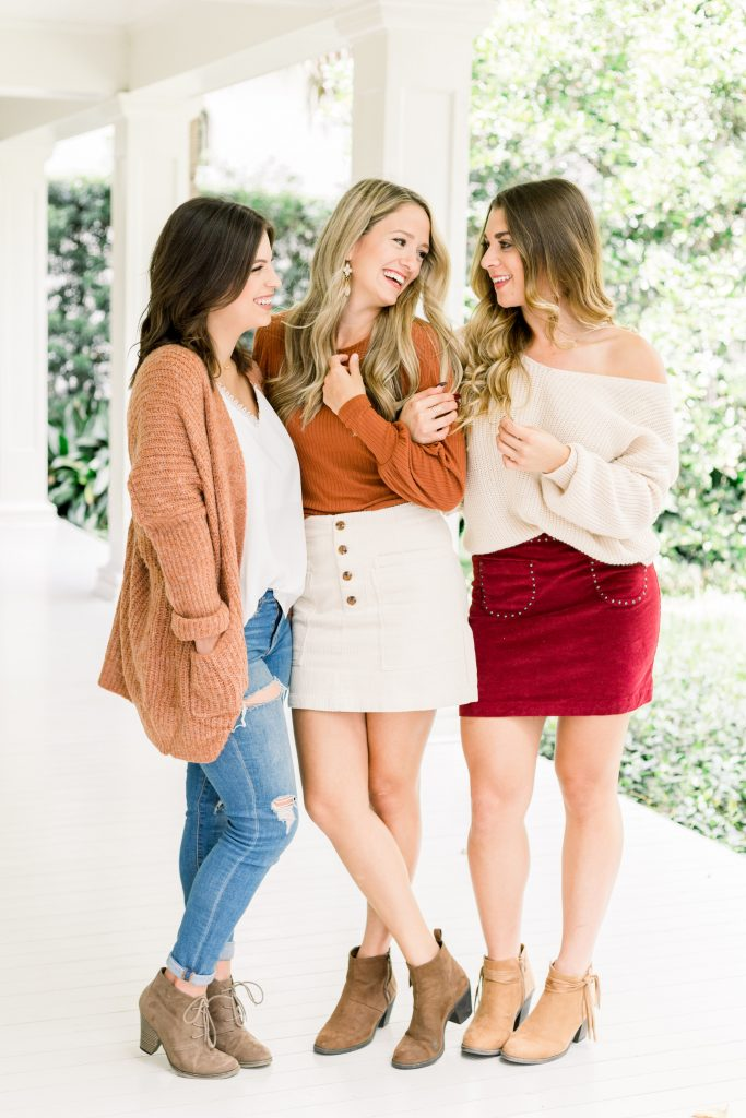 three young women standing on white porch dressed in fashionable fall colors