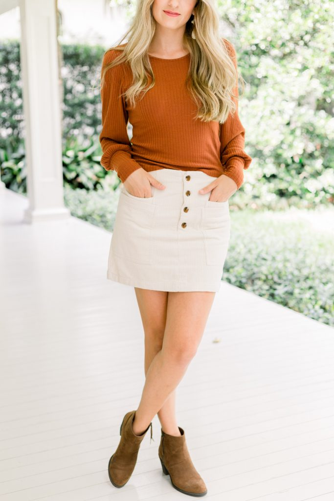 blonde female wearing orange bubble long sleeve top with ivory button front mini skirt and brown booties