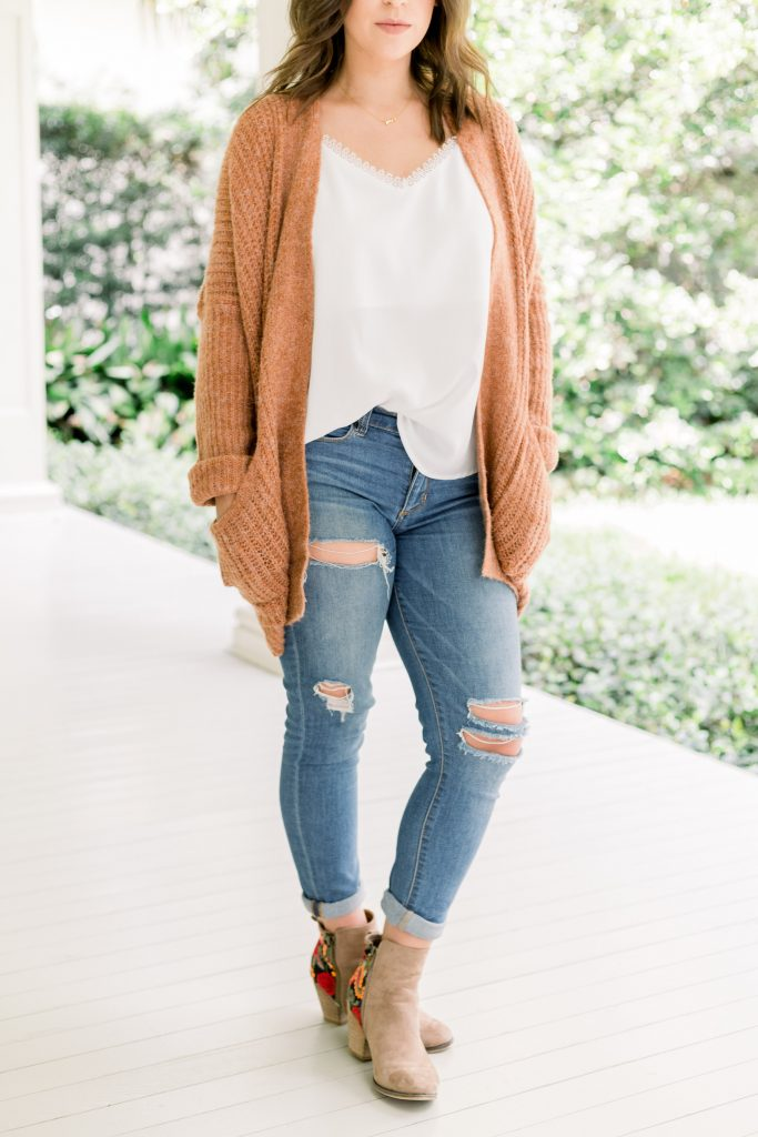 brunette female wearing white tank with orange colored cardigan ripped jeans and brown booties