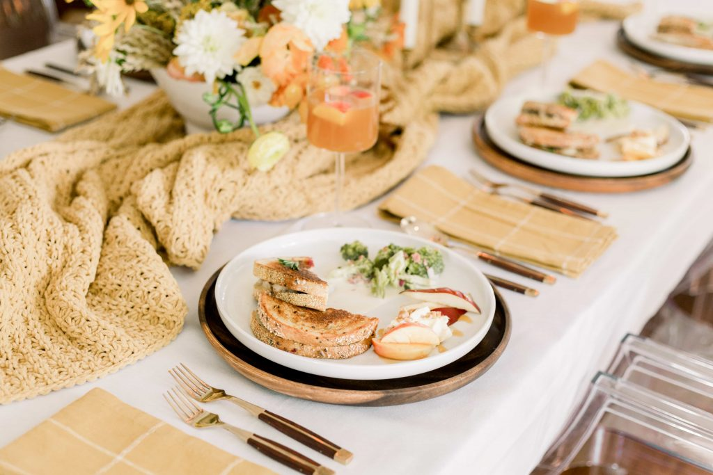 thanksgiving dinner on white plate on table with mustard linen napkins and table runner