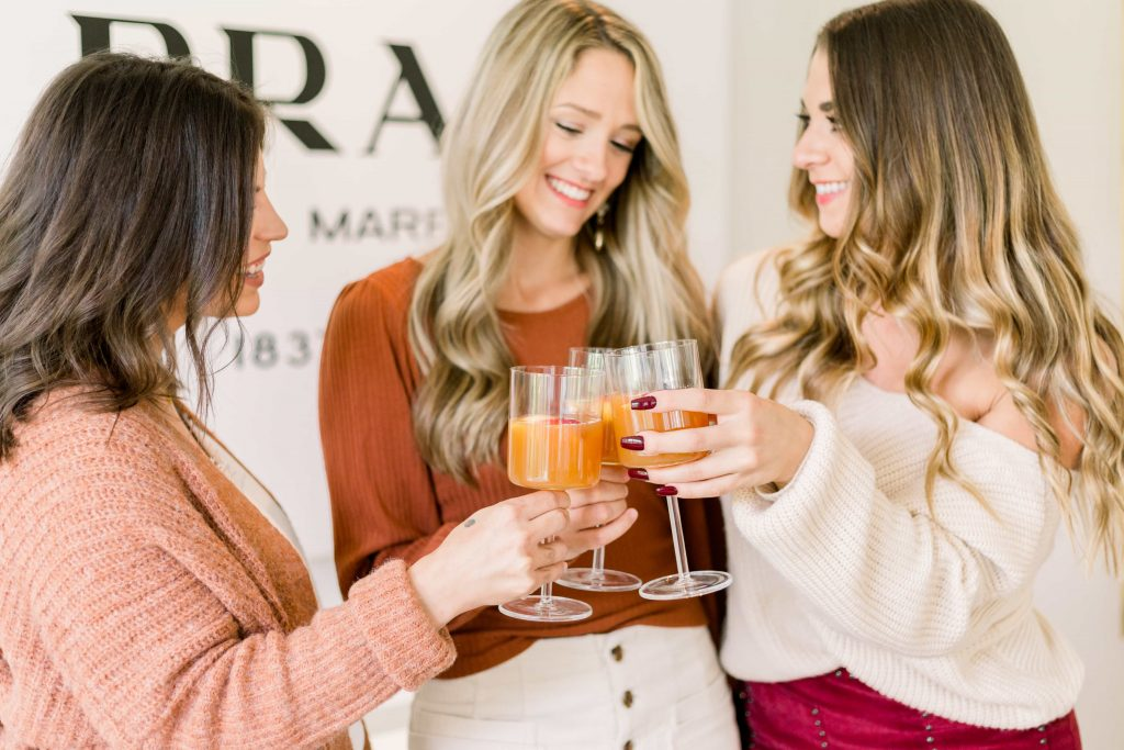 three young women wearing fall colored clothes toasting with apple cider sangria