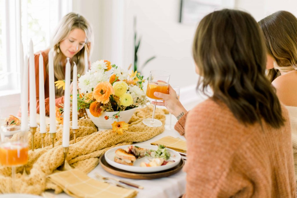 three women sitting at dining room table for thanksgiving dinner