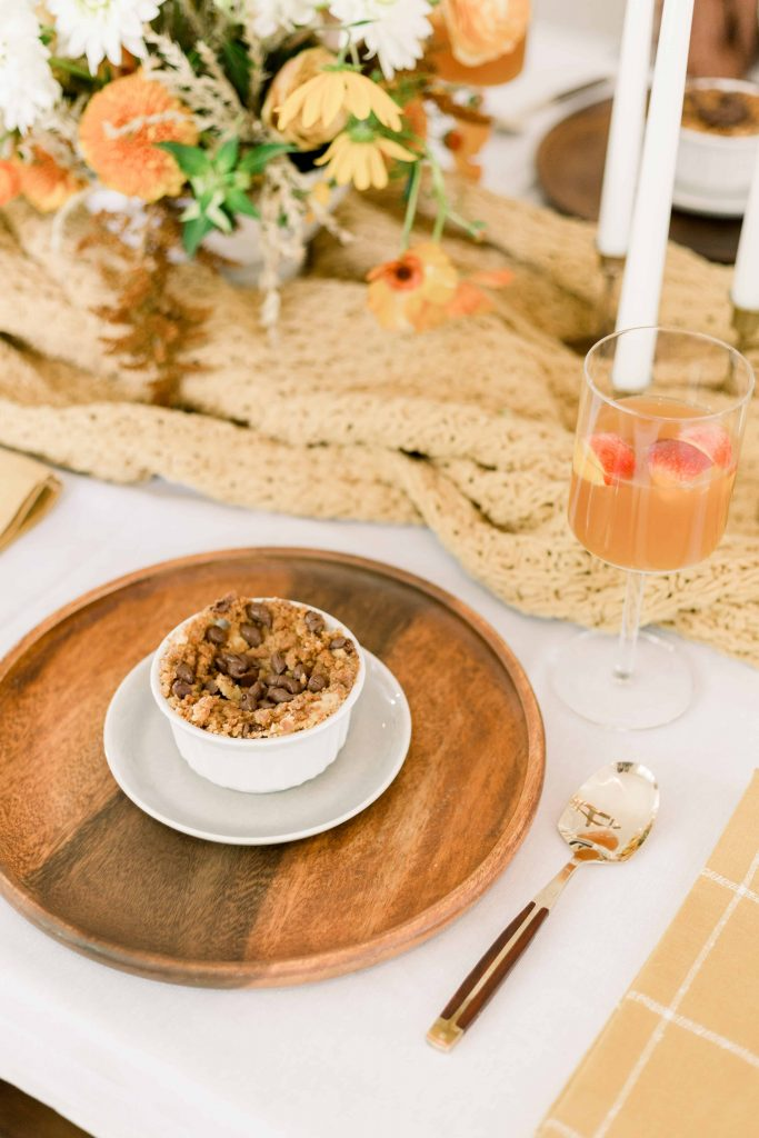 pumpkin dump cake in white ramekin dish on wooden charger at friendsgiving dinner