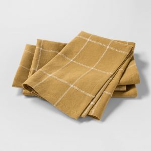 set of folded gold and white plaid linen napkins
