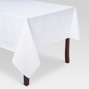 solid white rectangular table cloth on dark wood table