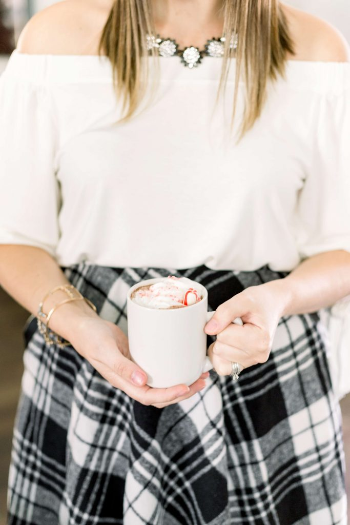 brunette female in an off white shirt and black and white plaid skirt holding a white mug with hot cocoa and whipped cream