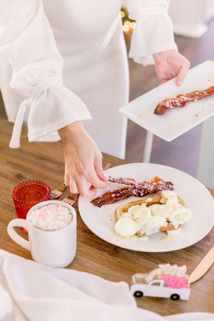 female in long sleeve ivory dress placing peppermint candied bacon on plate full of creamed eggs
