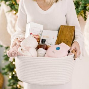 female in long sleeve cream dress holding cream woven basket full of holiday gifts